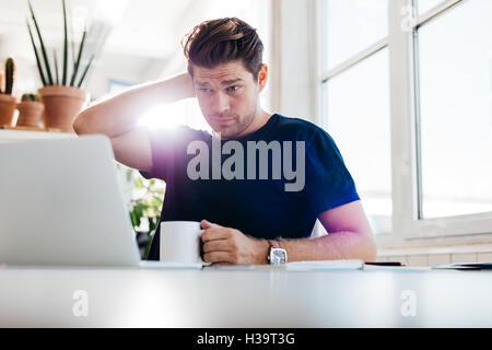 Joven sosteniendo la taza de café y mirando el portátil mientras está sentado en su escritorio en la oficina. Pensativo hombre de negocios en su trabajo plac