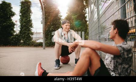 Jóvenes amigos sentados en la cancha de baloncesto. Los jugadores Streetball teniendo descanso después de un juego. Dos hombres jóvenes relajándose y tomando