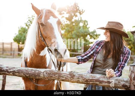 Sonriente joven atractivo cowgirl caminar a caballo en la granja