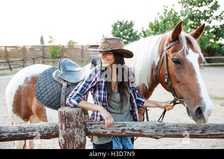 Retrato de mujer joven atractiva feliz cowgirl a caballo en el rancho