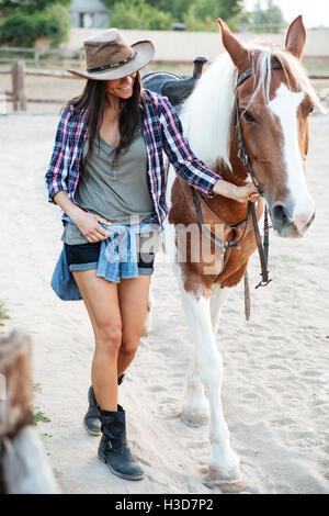 Alegre linda jovencita vaquera caminando con su caballo en el pueblo