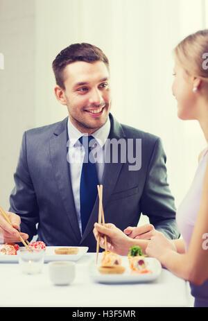 Pareja sonriente comiendo en el restaurante de sushi Foto de stock