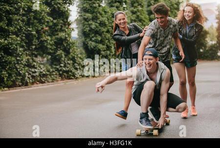 Disparo de longitud completa de adolescentes chicos en patineta con niñas empujando. Grupo multiétnico de amigos a divertirse al aire libre con skateb