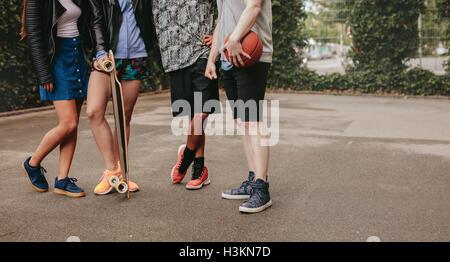 Captura recortada del grupo de gente de pie junto con el baloncesto y el monopatín. Un disparo con poco ángulo se centran en los hombres y mujeres de la pierna
