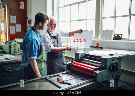 Artesano Senior/técnico mostrando joven tipografía imprimir en taller de artes del libro