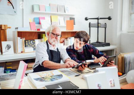 Senior masculino artesano hablando con jóvenes artesanos, mirando a la parte trasera del libro