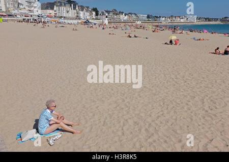Un jubilado mujer sentada sola en una playa en Francia