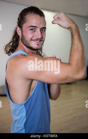 Retrato del hombre sonriente flexionando sus bíceps