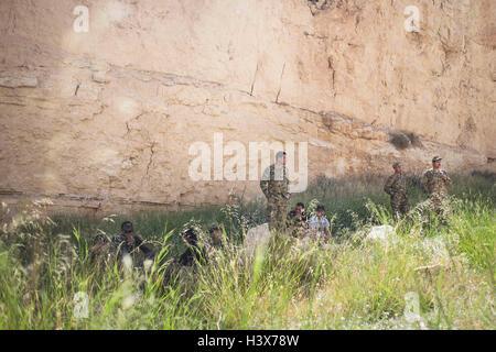 Amman, Ammán, Jordania. 21 abr, 2015. El equipo jordano descansa a la sombra de un acantilado de piedra arenisca antes del ''Urban Assault'' en el caso de la competencia de Guerrero el 21 de abril de 2015. En este caso, los soldados deben apresurarse a lo largo de un borde de tierra, tormentas de un edificio en un simulacro de ciudad, rescatar a un rehén y fuego a objetivos en la distancia. © Lindsey Leger/Zuma alambre/Alamy Live News Foto de stock