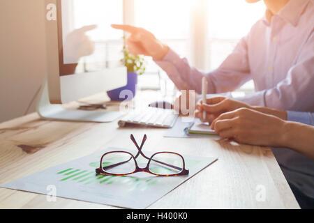 Puesta del sol en la atmósfera de trabajo co-oficina, reunión de negocios con dos personas, más cerca de las gafas