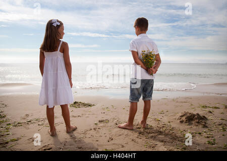 Niño sosteniendo flores detrás de su espalda, de pie junto a la niña en la playa Foto de stock