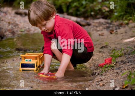 Muchacho caucásico jugar con juguetes de construcción en el río.