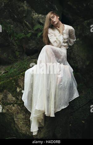 Bella mujer posando en las rocas y el musgo. Atmósfera de ensueño Foto de stock