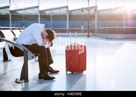 Viajero deprimida esperando al aeropuerto después de retrasos y cancelaciones de vuelos