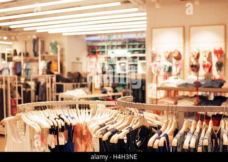La ropa en perchas en una tienda de ropa. El enfoque selectivo en el primer plano, de fondo borroso en el interior de la tienda. Tonos cálidos