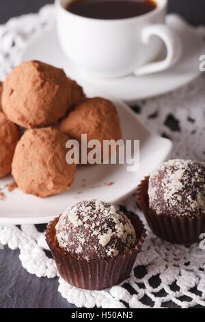 Deliciosas trufas de chocolate y café en una tabla vertical cerca.