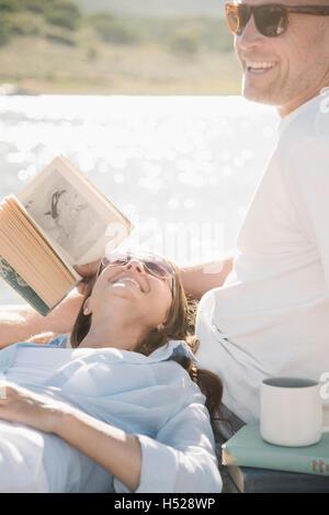 Hombre y mujer recostado sobre un embarcadero, leyendo un libro.