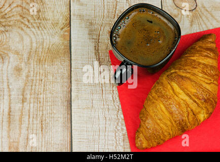 Croissant y una taza de café en una servilleta de papel rojo, colocado sobre una mesa de madera con placas de luz, plana y horizontal, vista desde arriba