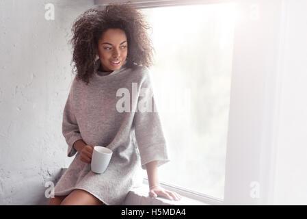 Chica mulata beber café en un alféizar de ventana