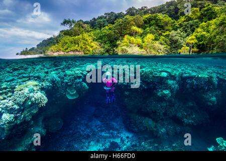 Captura de imagen dividida hembra rubia Scuba Diver explorar arrecifes de coral con isla tropical en segundo plano.