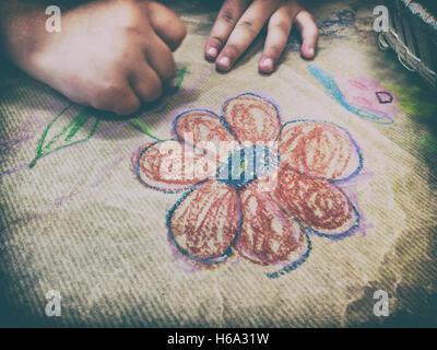 Dibujo infantil con una canasta de lápices de cera sobre la artesanía del papel de embalaje. Un alto ángulo de visualización