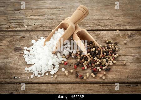 Gran sal de grano y pimienta mezclados en palas de madera rústica, en tabla, un alto ángulo de visualización Foto de stock