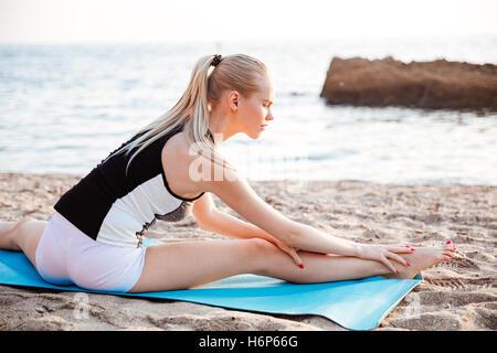 Retrato de una joven mujer rubia haciendo ejercicios de estiramiento en la esterilla de yoga al aire libre en la mañana