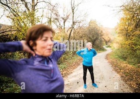 Las parejas ancianas marcha fuera en un soleado día de otoño, el estiramiento del bosque