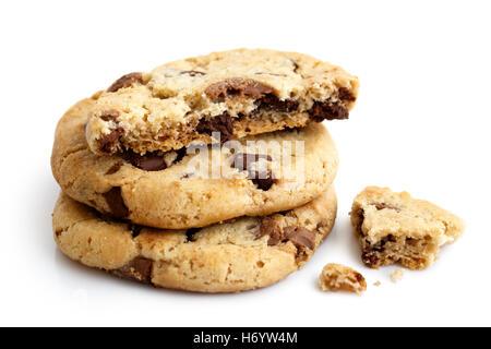 Una pila de tres galletas con trocitos de chocolate de luz aislados. La mitad con migas.