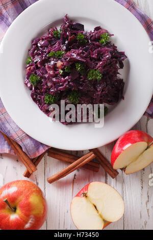 Guiso de repollo con manzanas de cerca en una placa vertical vista desde arriba Foto de stock
