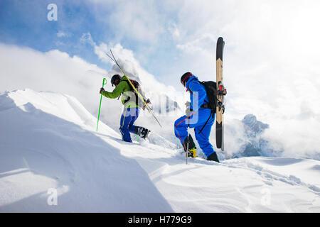 Dos esquiadores caminando en los Dolomitas con skies en su espalda, el Tirol del Sur, Italia Foto de stock