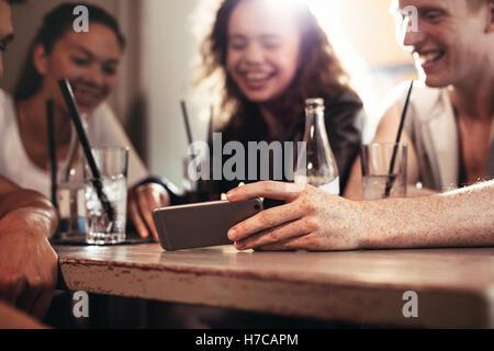 Un grupo de amigos, sentado en un bar y ver un divertido vídeo en el teléfono móvil, se centran en el teléfono móvil en la mano.