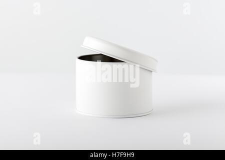 Abrir caja cilíndrica blanca sobre fondo blanco.