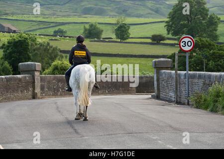 Vista trasera de hembras jóvenes, montando un caballo gris en una tranquila y pintoresca, Country Road - aldea Burnsall Valles de Yorkshire, Inglaterra.