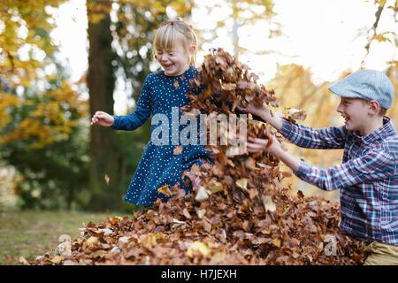 Feliz otoño. Dos niños jugando en el montón de hojas secas en otoño del parque.