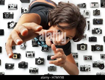 Greedy boy alcanzando una cámara entre una colección de diferentes cámaras analógicas antiguas