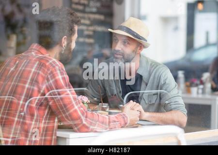 Una pareja gay sat manos en cafe