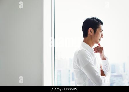 Un empresario en la oficina de pie junto a una ventana grande con brazos cruzados, mirando hacia la ciudad.