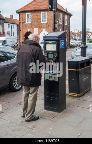 Un anciano compra un ticket de aparcamiento en la calle de una máquina Yarm Stockton on Tees Inglaterra