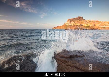 Olas de mar azul que enmarcan el pueblo encaramado sobre el promontorio, Castelsardo, Golfo de Asinara, provincia de Sassari, Cerdeña, Italia