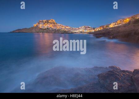 Bastidor de ondas de la aldea encaramada sobre promontorio al anochecer, Castelsardo, Golfo de Asinara, provincia de Sassari, Cerdeña, Italia
