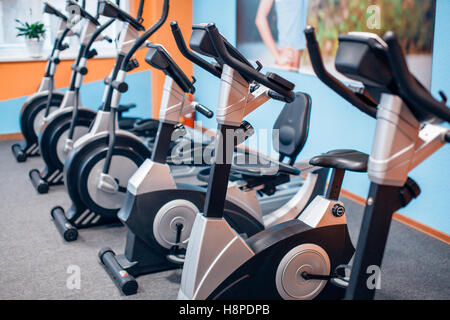 Aeróbic spinning bicicletas de ejercicio gimnasio con muchos en una fila Foto de stock