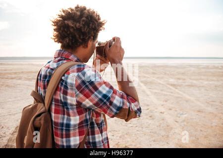Vista posterior del afroamericano joven con mochila tomando fotos en la playa