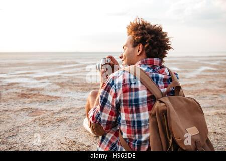 Vista posterior de la feliz joven africana tomando fotos en la playa