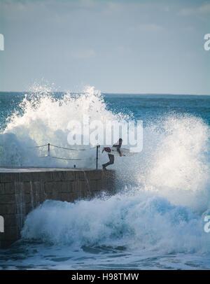 Porthleven, Cornualles, en el Reino Unido. 20 de noviembre de 2016. El clima del Reino Unido. Los surfistas teniendo arriesgada en ruta hacia el mar después de la tormenta Porthleven Angus pasa de Cornualles. El espigón en el puerto de entrada está normalmente cerrada durante un tiempo tormentoso como varias personas han sido asesinadas en el pasado por ser lavadas. Crédito: Simon Maycock/Alamy Live News