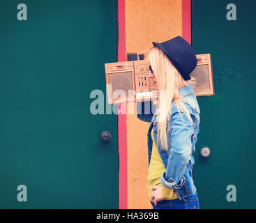 Una rubia hipster chica con gafas es escuchar una vendimia oro boombox radio con un altavoz para un concepto de entretenimiento musical. Foto de stock