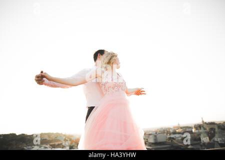 Pareja joven en amor posando en el techo con vista a la ciudad perfecta la celebración de manos y abrazos . Hermoso atardecer