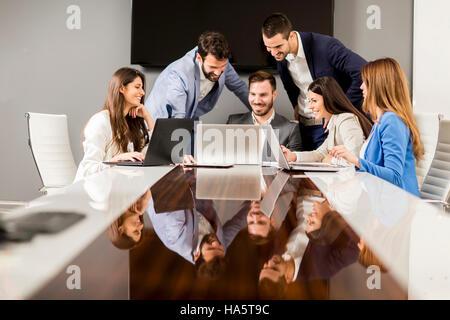 Jóvenes colegas sentados en reunión de negocios en la oficina moderna Foto de stock