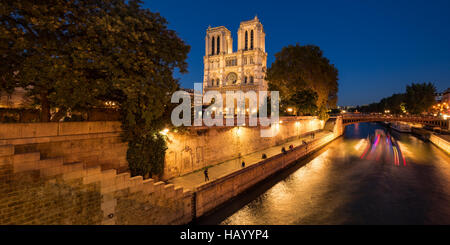 Catedral de Notre Dame de París iluminado en la penumbra con el Sena y el Pont au Double. Ile de la Cité, París, Francia