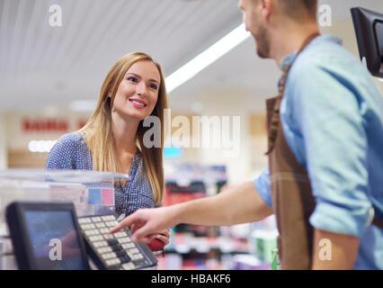 La mujer junto a la caja registradora hablando con la vendedora